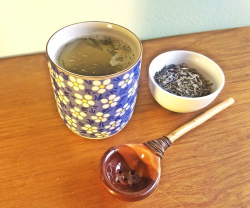 green tea, a cup of tea, and a spoon