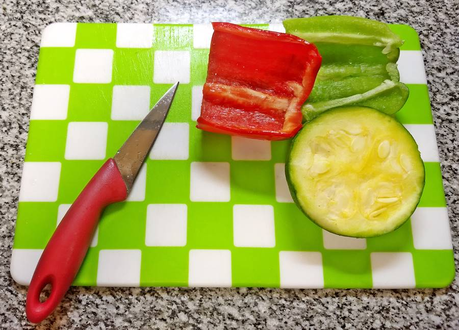 red pepper, green pepper and half a green summer squash on choping board