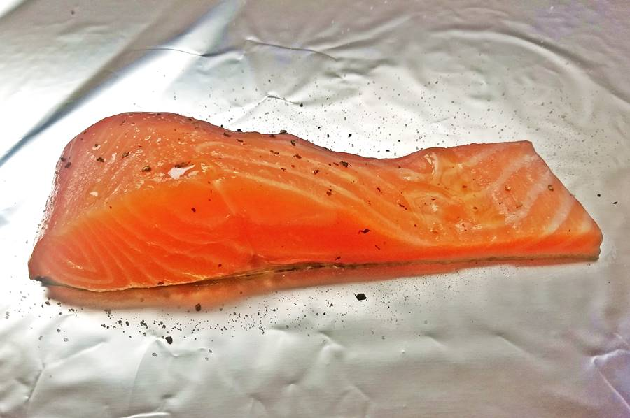 raw salmon on aluminium foil, with salt pepper and olive oil