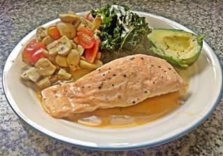salmon, avocado, kale and mushroom - tomato wok on a plate