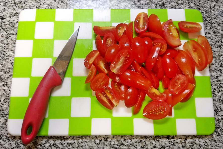 cherry tomatoes sliced on board