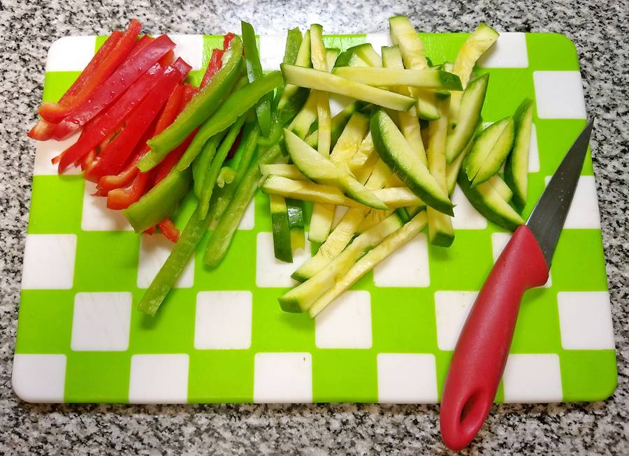 sliced red and green peppers and green summer squash on board