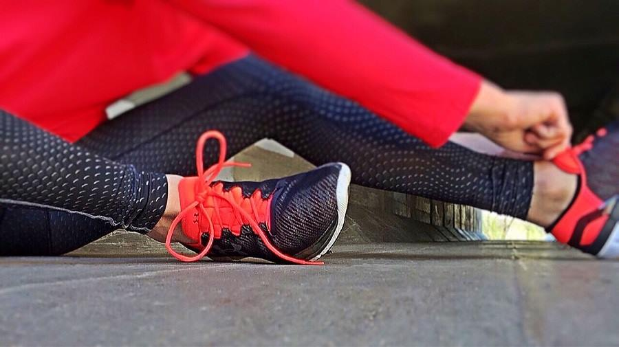 fitness: woman in red gym tights tying her sports shoe laces
