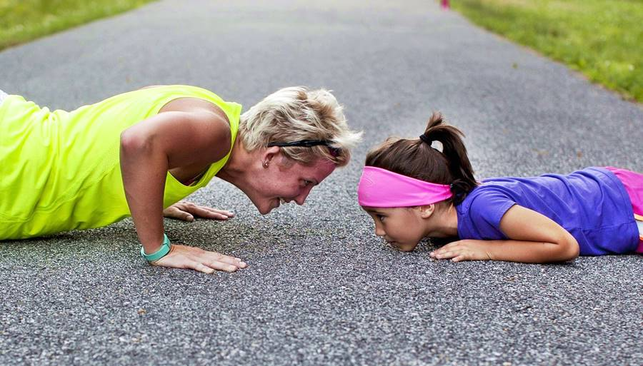 older woman and child facing each other smiling as they do push ups on tarmac floor