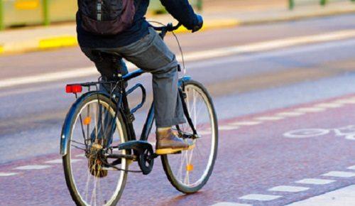 person riding a bike down a city cycling trail