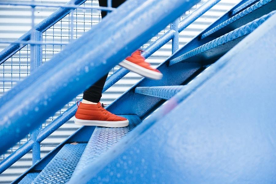 woman's feet in sports shoes climbing up the steps of a metal staircase
