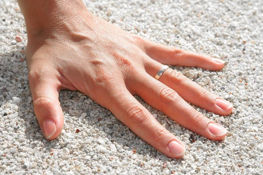 woman's hand resting on white sand