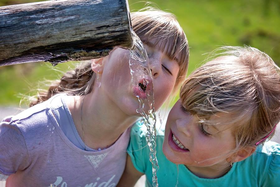 Young smiling girls drinking water