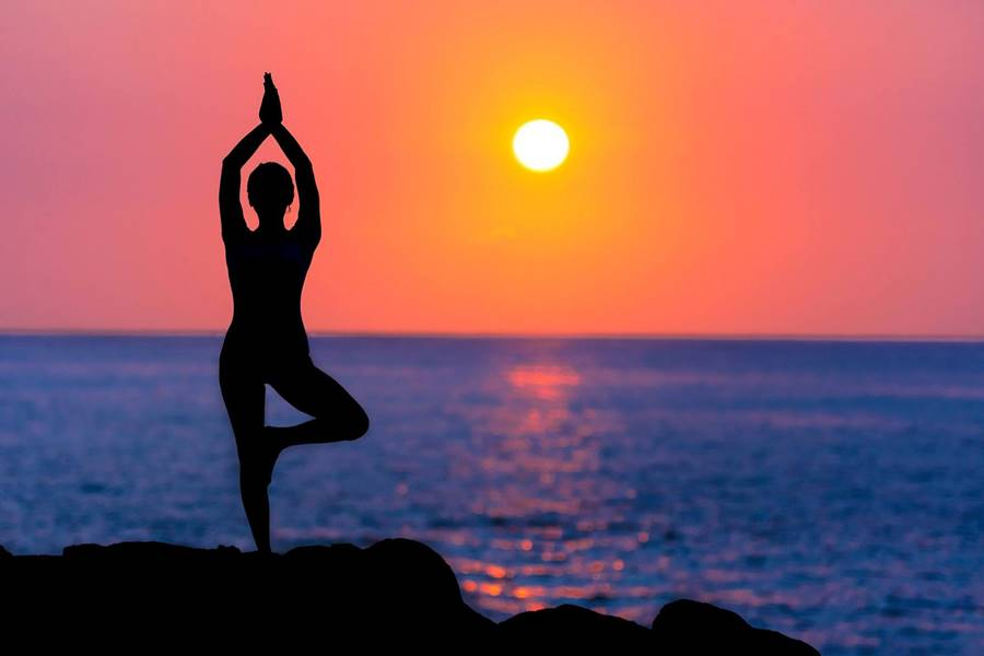 allegory of perfect balance: woman doing yoga pose at sunset