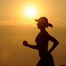 staying healthy: a woman running during sunrise