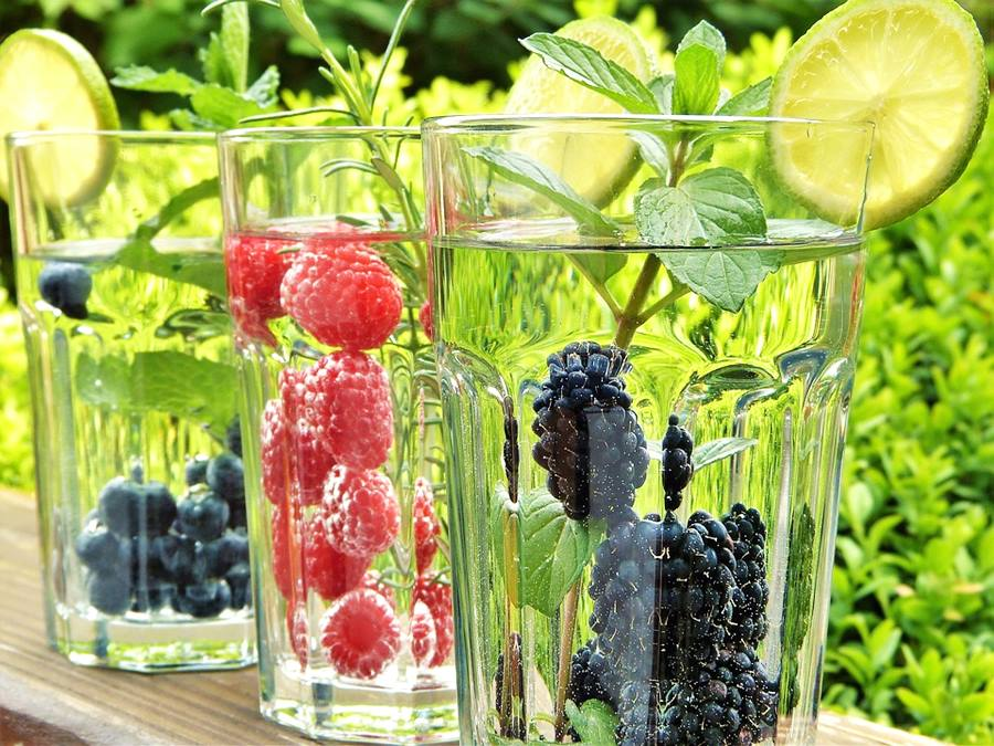glasses of water with slice of lime, mint and whole berries
