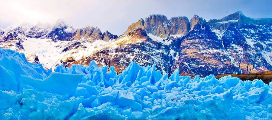 Glacier with blue ice and rugged snow capped mountains in Patagonia