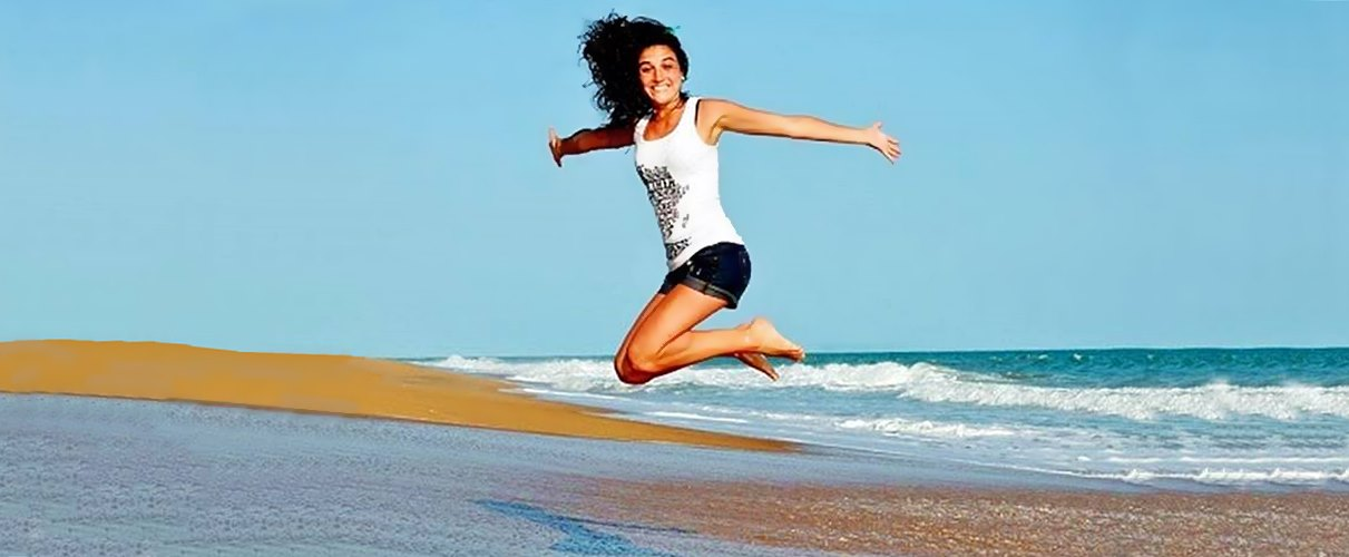 woman jumping on beach, smiling
