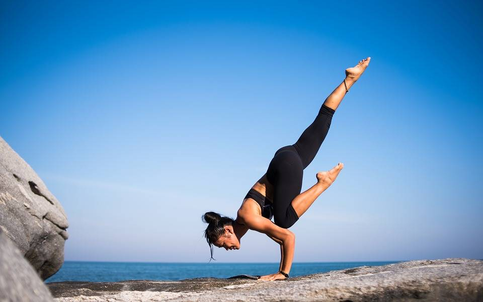 Woman in striking yoga pose handstand by the sea