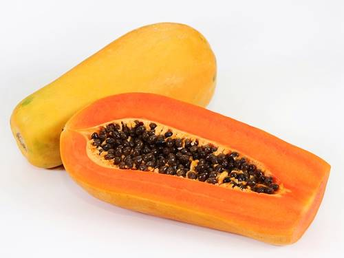 a whole papaya and one split in half showing its seeds