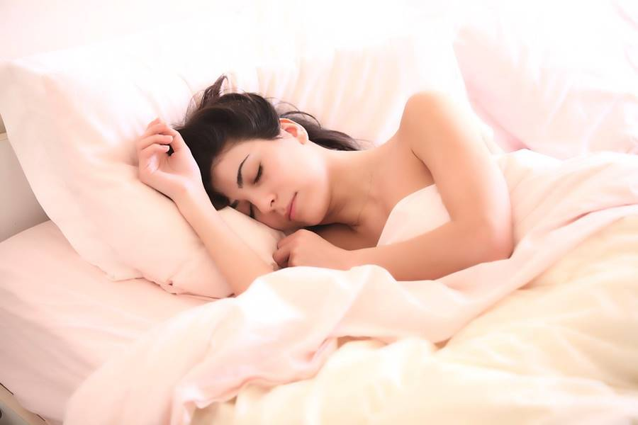 woman sleeping soundly on white sheets