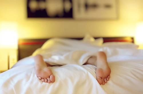 feet jutting out of under a sheet of a sleeping person