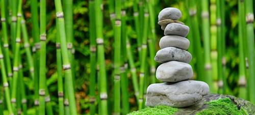 zen stones cairn and green bamboo canes