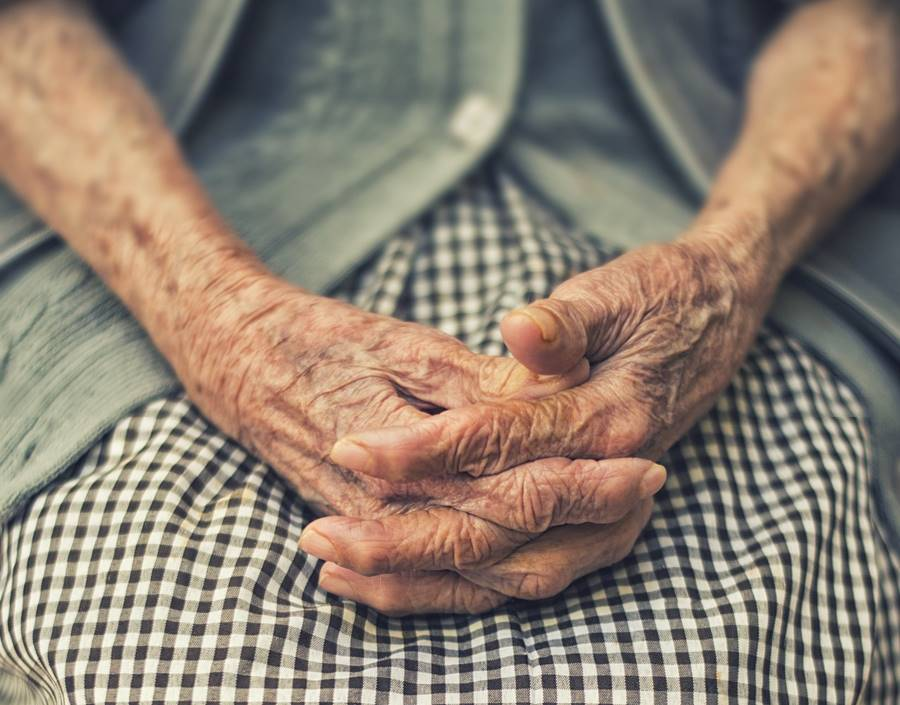 Old woman clasping her wrinkled hands