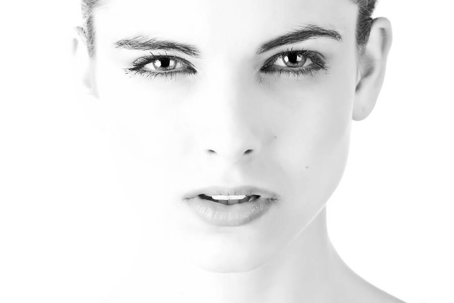 face of a beautiful young woman in black and white